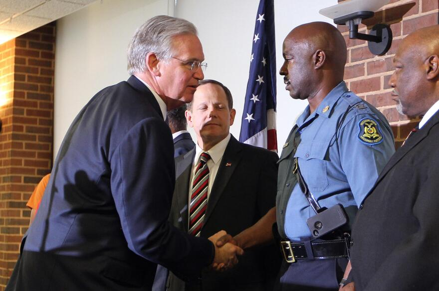 Gov. Jay Nixon shakes the hand of Capt. Ron Johnson after putting Johnson in command in Ferguson on August 14, 2014