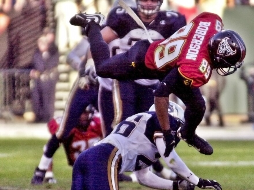 The XFL is set for a surprising second life, kicking off games this weekend. In this file photo, San Francisco Demons wide receiver Brian Roberson jumps over Los Angeles Xtreme cornerback Dell McGee during a 2001 game.