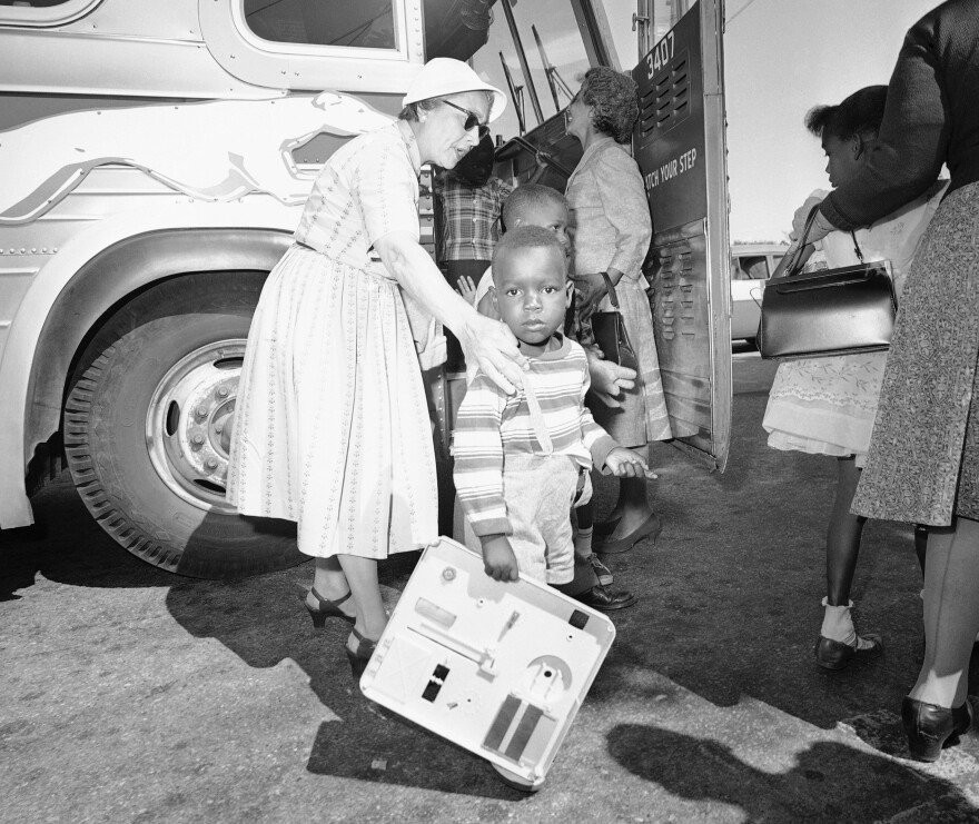 Two unidentified women, residents of Hyannis, Mass., help some of the nine children of Lela Mae Williams (not in photo) off the bus, June 8, 1962 at Hyannis on their arrival from Huttig, Ark.