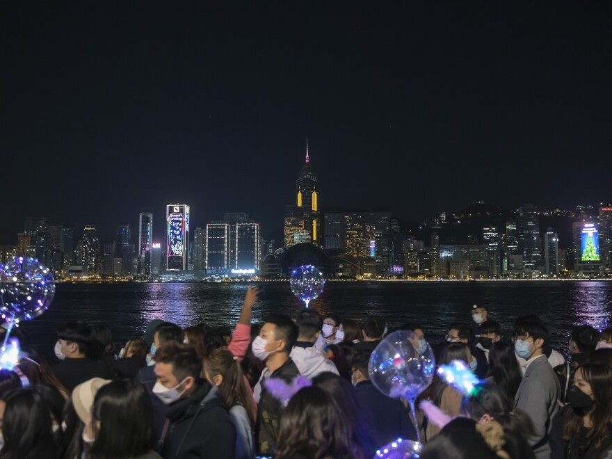 A crowd walks through Hong Kong's Victoria Harbor, a spot usually dedicated to larger New Year's celebrations, including fireworks, which were canceled this time.