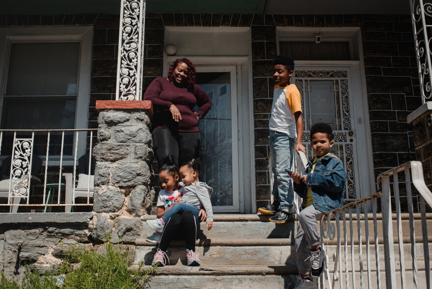 Marquita Matthews stands outside with her children, 8-year-old Masyn, Gabrielle, 2, Levi, 11, and Eli, 4, at their home in Philadelphia on April 2. Matthews says it has been an adjustment for her to be home because she works overnight as a pharmacy tech, while her husband works as an electrician.