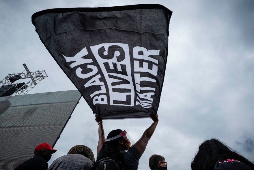 A march participant holds a Black Lives Matter banner during the speeches.
