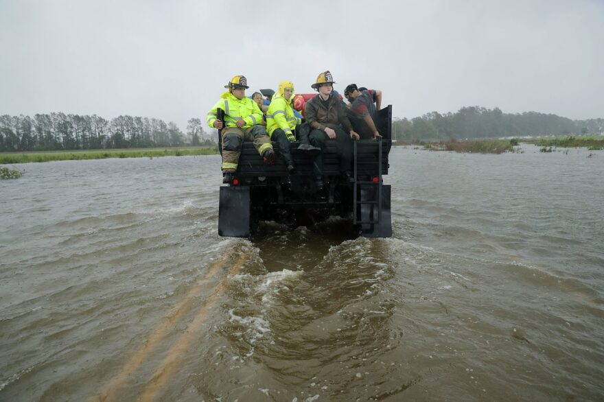 Rescue workers from the Township No. 7 Fire Department and volunteers from the Civilian Crisis Response Team use a truck to move people rescued from their flooded homes during Hurricane Florence on Sept. 14, 2018 in James City, N.C. (Chip Somodevilla/Getty Images)
