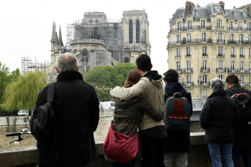 People gather across from Notre Dame Cathedral in the aftermath of a fire that devastated the cathedral.