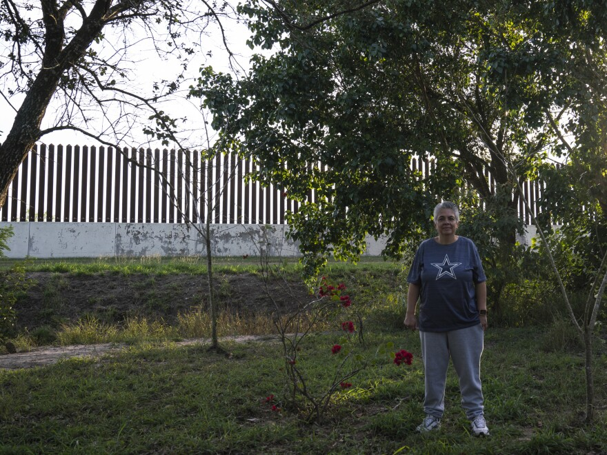 Gracie Garcia poses for a photo in her backyard in Los Indios, near San Benito, Texas. The border wall was built about 10 years ago on Garcia's property, and she says she has not been paid for it.