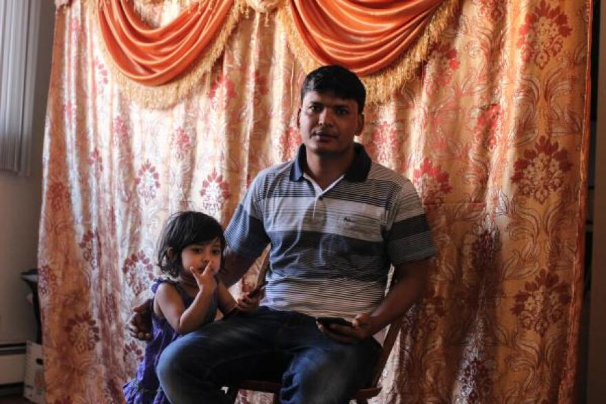 Basar poses with his two-year-old daughter at his home in Greeley, Colorado.