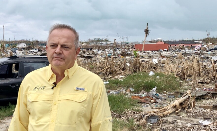 A man stands in front of debris