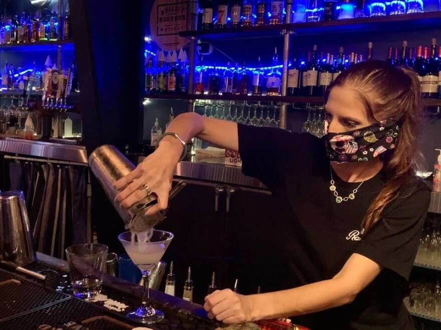 Woman bartender wearing mask pouring cocktail.