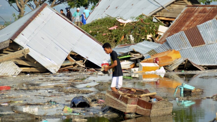 A man surveys damage caused by the earthquakes and tsunami in Palu, central Sulawesi, Indonesia, Saturday. Hundreds of people were killed.