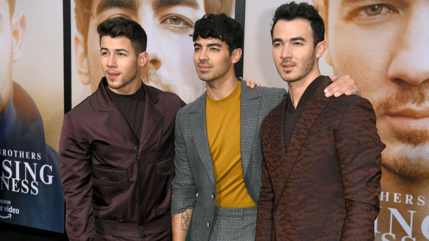 (From left) Nick, Joe and Kevin Jonas attend the premiere of the Jonas Brothers documentary, Amazon Prime Video's <em>Chasing Happiness,</em> in June 2019 in Los Angeles.