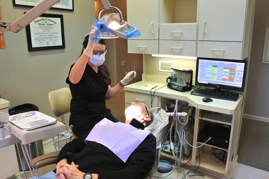 Suzanne Cline, a hygienist with Jonesboro Dental Care, prepares to clean Dr. Richard Stevenson's teeth.