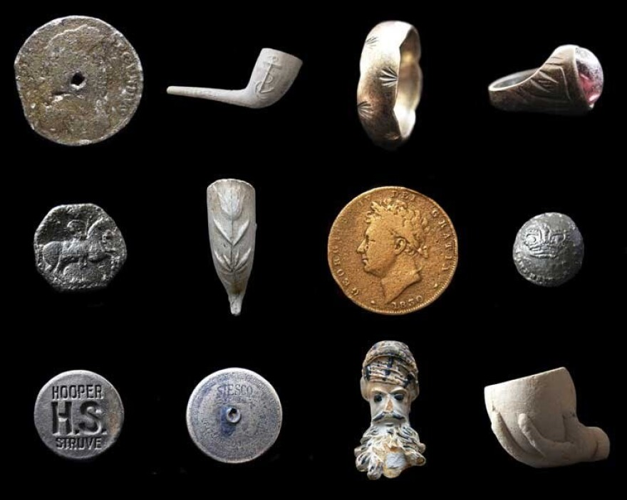 Found objects from the Thames. Top row: a 1687 tin halfpenny, a Victorian clay pipe, a gold ring, a Victorian ring. Middle row: a decorated medieval button, a Victorian clay pipe, an 1830 George IV farthing, a Georgian military button. Bottom row: a Hooper Brewery stopper, a sailor's bag lock, a French Jacob pipe bowl and a child's toy clay pipe bowl. <em>Note: objects not to scale.</em>