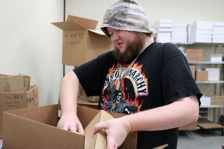 Michael Palone, 26, who has mild autism, originally diagnosed as Asperger's syndrome, is paid to assemble packages through a program run by The Arc in Union City, Calif. The program may close soon due to budget problems.