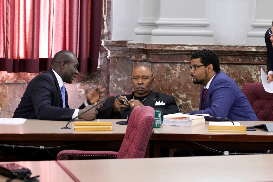 St. Louis Board of Aldermen President Lewis Reed, left, talks with Aldermen Sam Moore, center, and Antonio French about a stadium funding deal. All three voted in favor of the proposal aimed at keeping the St. Louis Rams in town.