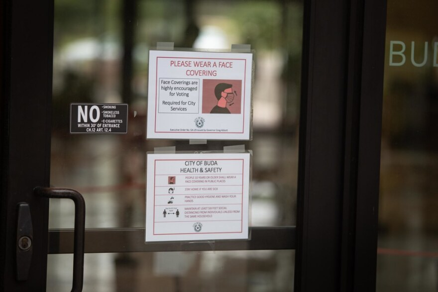 Signs telling visitors to wear masks on the door of Buda City Hall