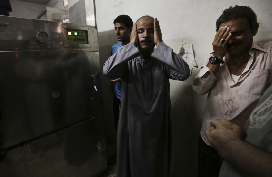 In the morgue of Gaza's Shifa hospital, Palestinian relatives mourn following an explosion that reportedly killed at least 10 people Monday, nine of them said to be children.
