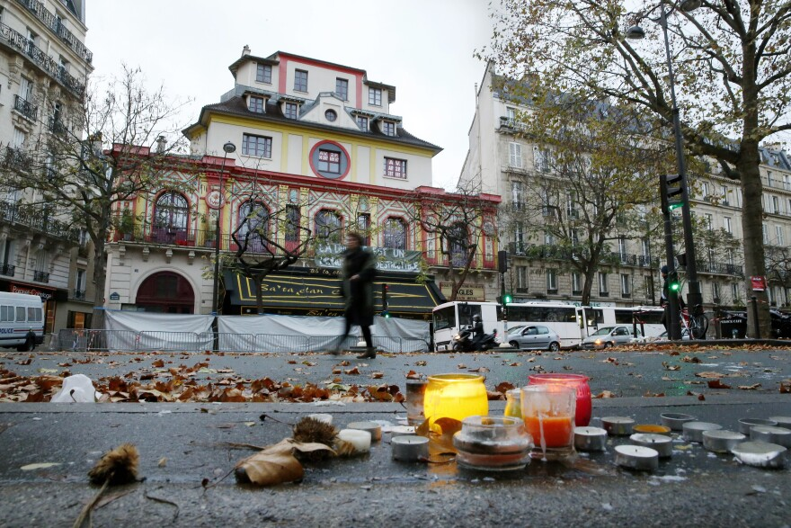 A woman walks past the Bataclan theater in Paris on Tuesday. At least 82 people were killed in the theater during coordinated attacks on Friday.