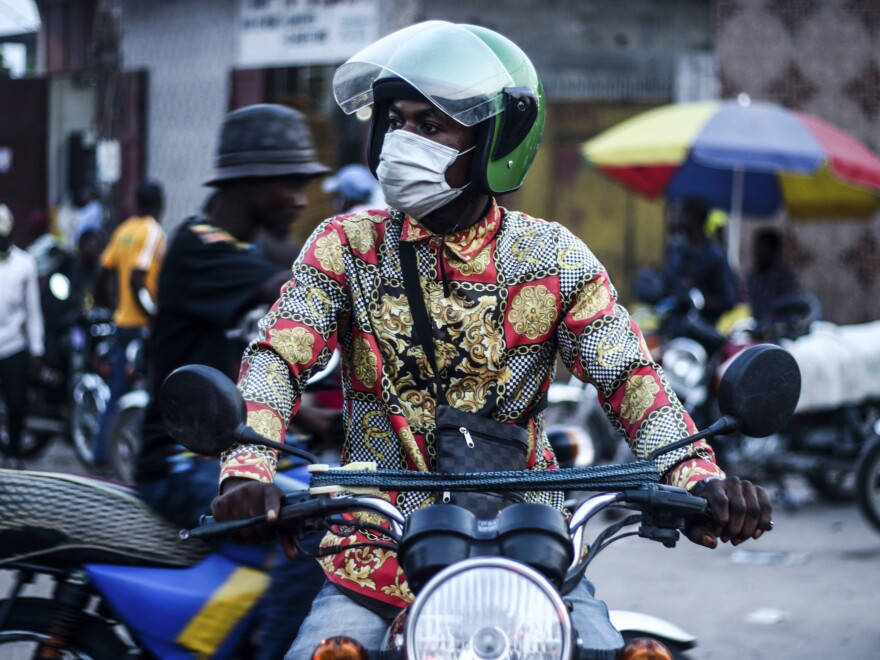 A masked motorcycle taxi driver in Kinshasha.