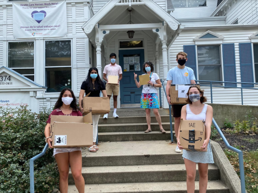 People wearing masks holding large cardboard boxes stand on a set of stairs outside a building.
