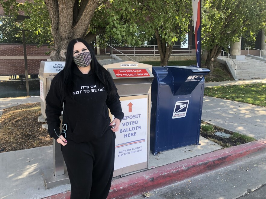 A photo of Brandie Hoffman in front of a ballot drop off box.