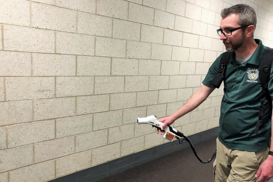 Tony Vassiliadis, the head nighttime custodian at Wellesley High School in Wellesley, Mass., demonstrates an electrostatic sprayer. During an actual cleaning, he would he would wear gloves and an N95 mask.
