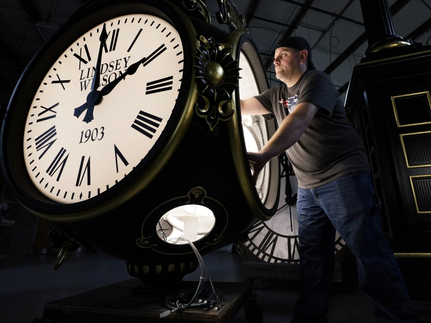Dan LaMoore works on a Seth Thomas Post Clock at Electric Time Company on Oct. 23, in Medfield, Mass. Daylight saving time ends at 2 a.m. local time Sunday.