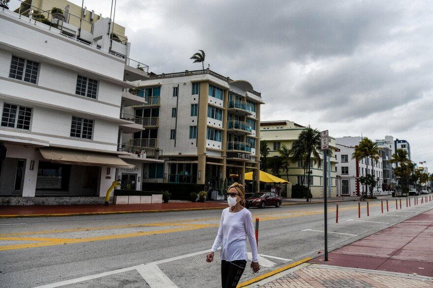 A woman in a face mask walks on a deserted Ocean Drive last week in Miami Beach, Fla. War game simulation in the early 2000s foresaw an overwhelmed health care industry struggling to respond to unprecedented demand.