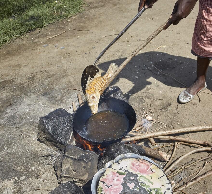 Naomy Akoth prepares fish to sell at the market.