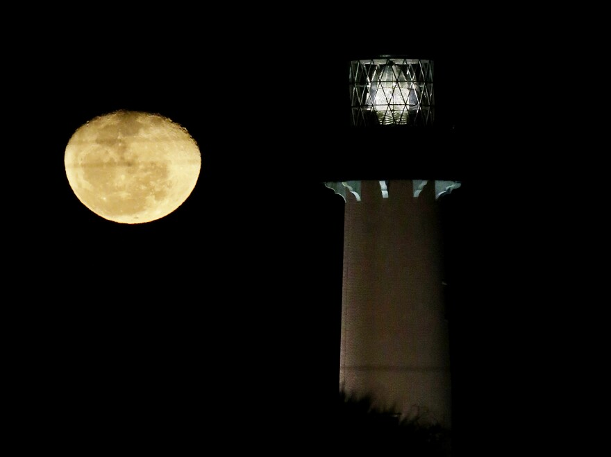 The moon, in its waning gibbous state, rises near the Jupiter Lighthouse in 2013, in Jupiter, Fla. The 108-feet tall, brick structure was first lit in 1860. The lighthouse sits atop a Native American archaeological site, which is at risk from the rising sea level.