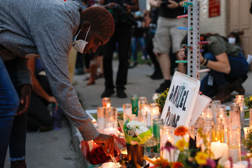 A demonstrator lights a candle in front of a memorial on Sept. 3, while taking part in a protest against police over the death of Daniel Prude in Rochester, New York.