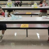 Young kids are sitting in a school cafeteria several feet apart from each other during the first week of schools reopening in Miami-Dade County.