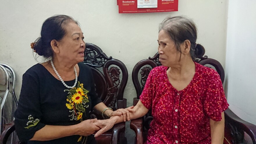 Dao, left, sits with club member Ms. Báu, who is seeking financial assistance from the club. Some funds are available to members in need.