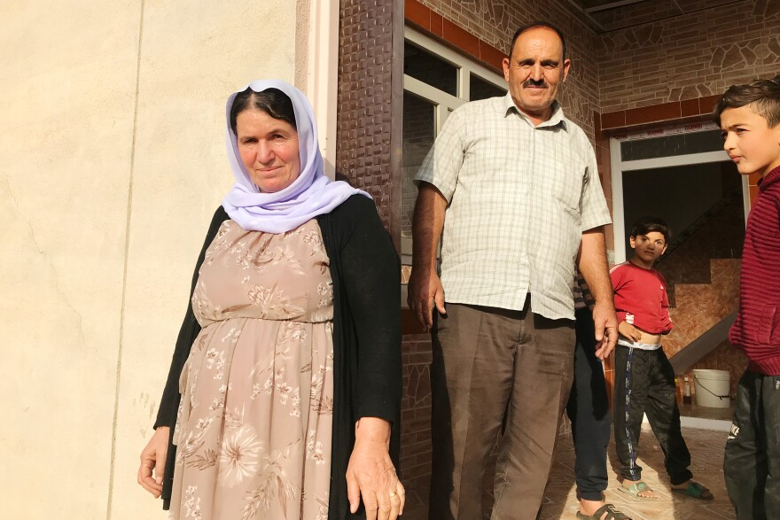 Nofa Khudeda (left) and her husband Ali Edo with neighborhood children just minutes after the couple arrived home in their village of Tel Qasab after six years in a camp for displaced Yazidis.