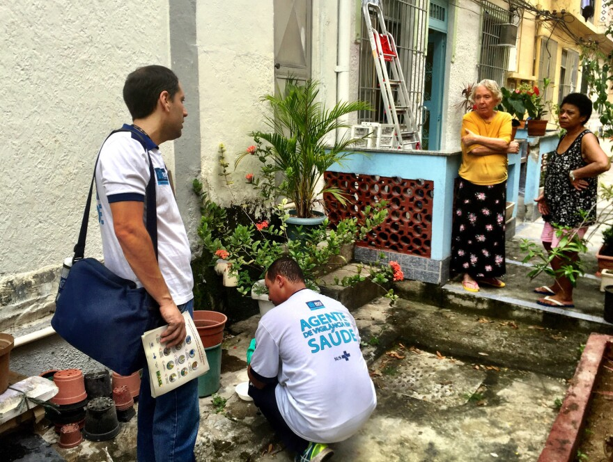 Health inspectors collect samples of mosquito larvae from standing water in a garden in a middle-class neighborhood in the north of Rio de Janeiro. They are searching for places where the <em>Aedes aegypti </em>mosquito breeds — that's the one that carries Zika virus.