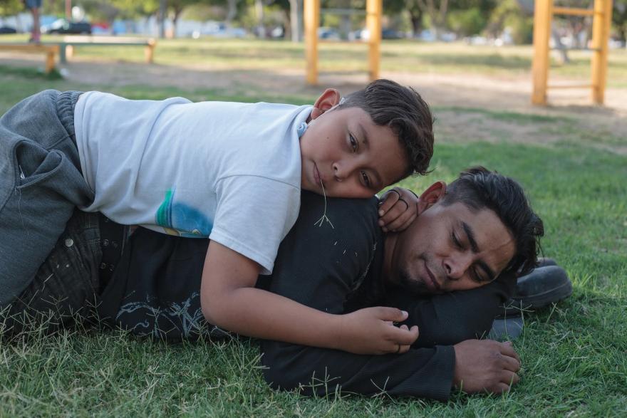 Donovan se recuesta sobre la espalda de su padre César en un parque en Juárez