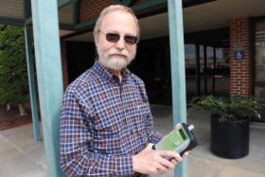 Pediatrician Dr. Warren Skaug with the air quality machine he uses to log the effects of agricultural smoke.