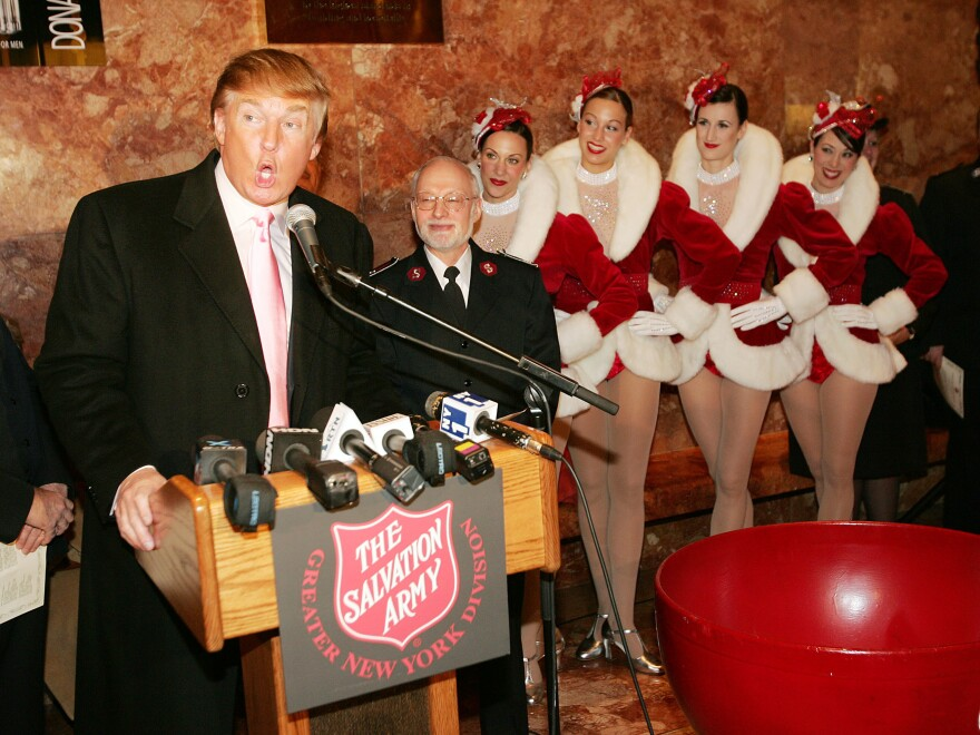 The Radio City Rockettes listen as Donald Trump speaks during a ceremony to help The Salvation Army kick off its annual Christmas kettle effort at the Trump Tower Atrium Nov. 23, 2004.