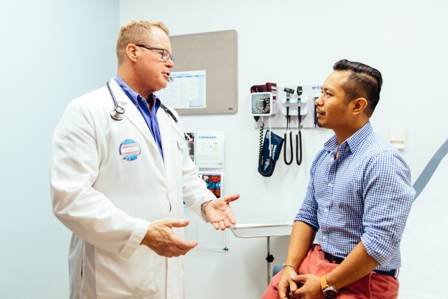 A doctor in a white lab coat and trans pride sticker talks to a patient in an exam room.
