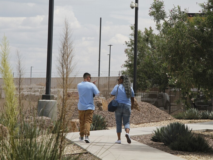 "Two Border Patrol subcontractors, or ""monitors,"" brought for the first time to care for children, walk outside at the Border Patrol station in Clint, Texas."