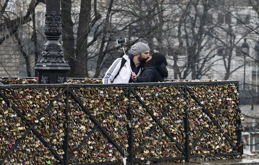 A couple kiss in front of love padlocks on the Pont Neuf in Paris. The city of Paris is organizing an auction of love locks from the Pont des Arts and other bridges, with profits going to groups that aid refugees.