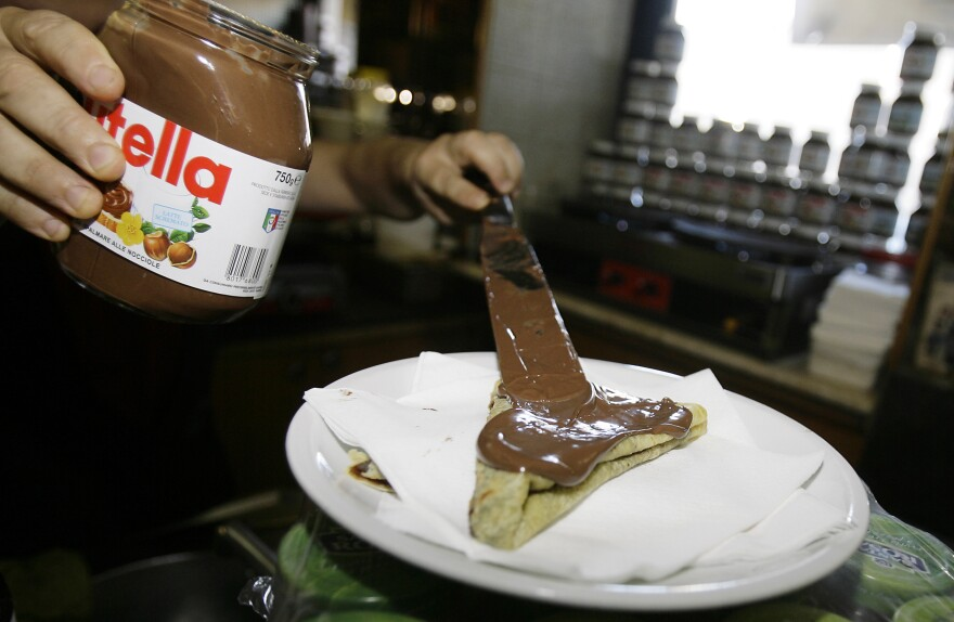 The bartender spreads Nutella on a crepe in a creperie in Rome.