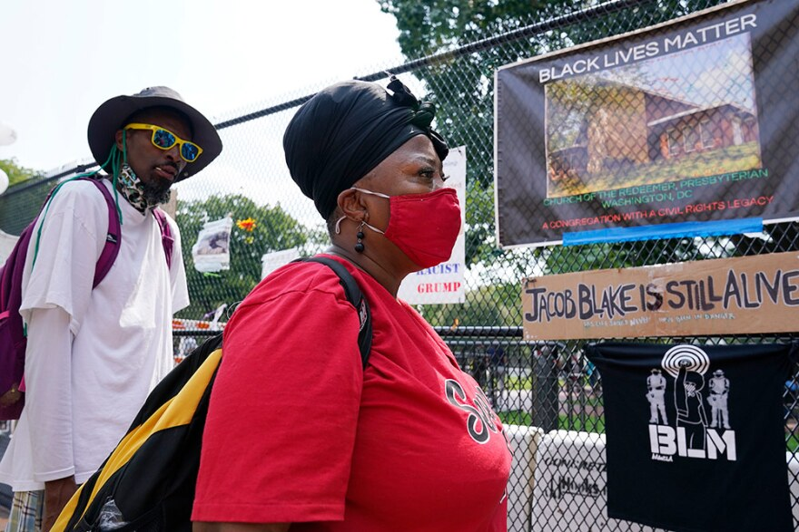 women in red shirt and mask looks at BLM art on a fence. A man looks on behind her.