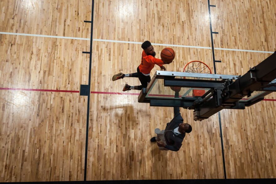 Darrius Johnson, 26, makes a layup with Adam Walker, 31, before their pick-up game Saturday at Monsanto Family YMCA.