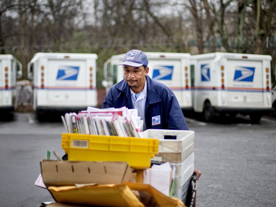 USPS carrier Michael McDonald gathers mail before making his delivery run in February in Atlanta.