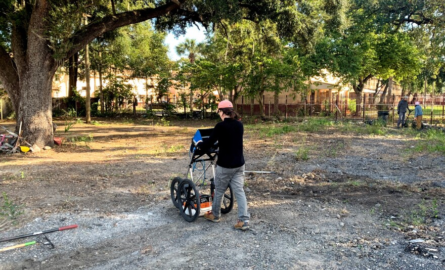 Rebecca O'Sullivan, dressed in warm gear and jeans, pushes a ground penetrating radar device that resembles a baby jogging stroller over an empty lot shaded by an oak tree.