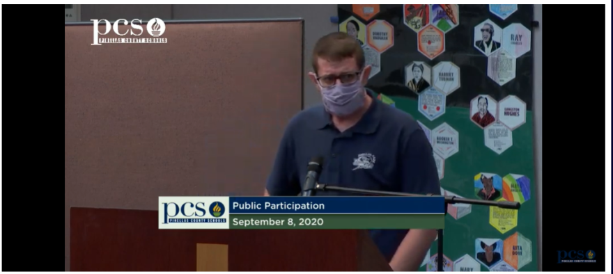 A middle school teacher in a blue shirt and face mask talks at a Pinellas School Board meeting.
