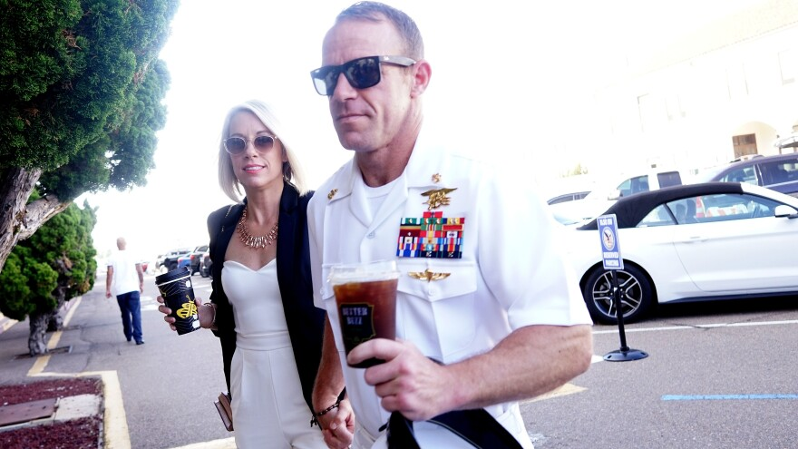 Navy SEAL Special Operations Chief Edward Gallagher walks into a military court building in San Diego along with his wife, Andrea Gallagher, on Tuesday. A military jury acquitted him of all but one count of war crimes — posing with the body of a dead 17-year-old ISIS prisoner.