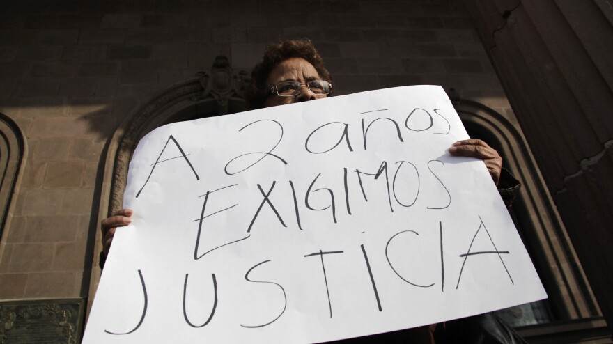 """A woman holds a sign that reads, """"We demand justice after two years,"""" during a Jan. 11 protest outside the government palace in Monterrey denouncing the disappearance of family members in the state of Nuevo Leon."""