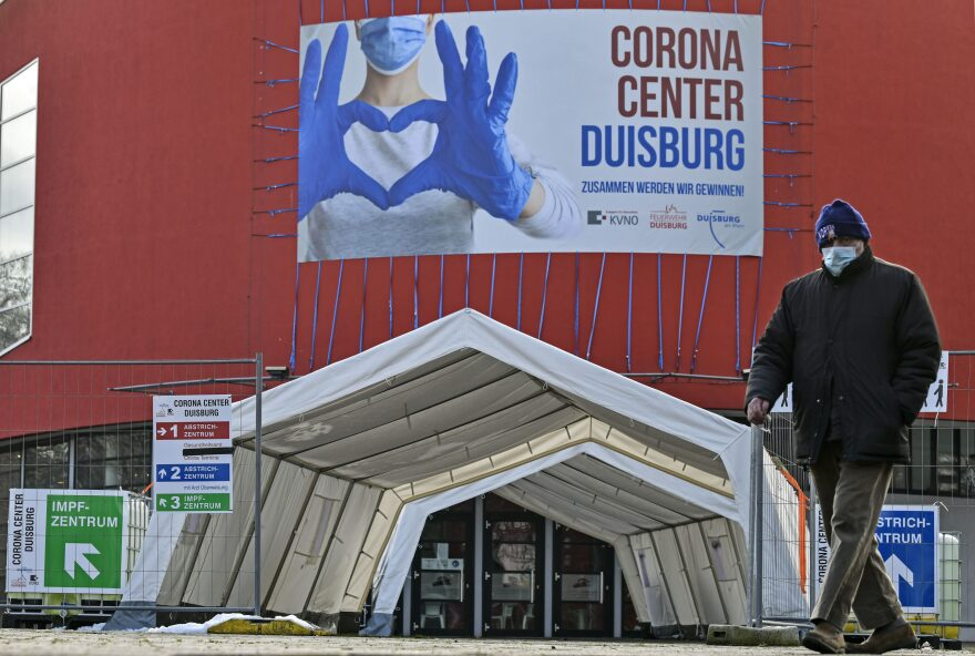 A man wearing a face mask walks past the Corona Center in Duisburg, Germany. The former theater has been turned into a COVID-19 test and vaccination center. Thousands of elderly Germans faced online error messages and jammed up hotlines in late Jan. 2021 as technical problems marred the start of the coronavirus vaccine campaign. (Martin Meissner/AP)