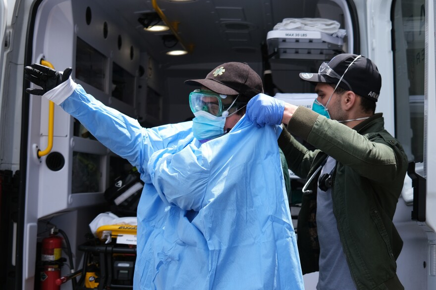 Medics suit up in personal protective equipment as they prepare to pick up a patient in severe respiratory distress from a group home in the Borough Park neighborhood of Brooklyn on May 11.